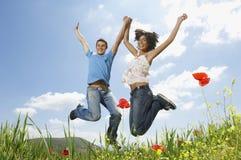 跳跃在鸦片领域的年轻不同种族的夫妇 图库摄影
