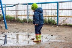 跳跃在水坑的小孩男孩 库存照片