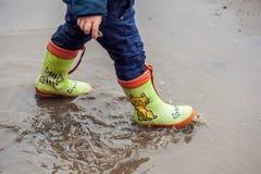 跳跃在水坑的小孩男孩 免版税库存照片