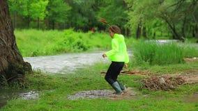 跳跃在水坑的愉快的女孩在河附近 影视素材