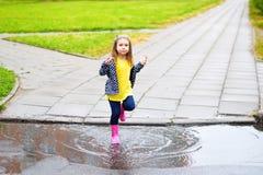 跳跃在水坑的愉快的逗人喜爱的小女孩在雨以后在夏天 免版税图库摄影