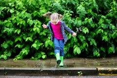 跳跃在水坑的愉快的逗人喜爱的小女孩在雨以后在夏天 免版税库存图片