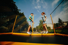 跳跃在绷床的夫妇在公园 免版税库存图片