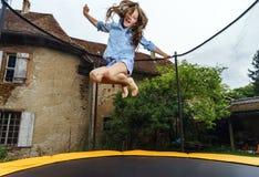 跳跃在绷床的逗人喜爱的十几岁的女孩 免版税库存图片