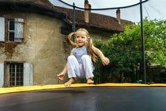跳跃在绷床的逗人喜爱的学龄前儿童女孩 免版税图库摄影