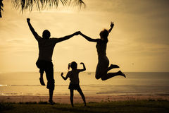 跳跃在黎明时间的海滩的愉快的家庭 库存图片
