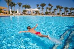 跳跃在水池的小男孩在旅馆里 库存照片
