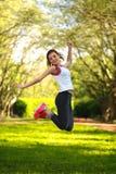 跳跃在绿色夏天公园的愉快的嬉戏女孩 免版税库存图片