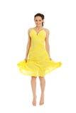 跳跃在黄色礼服的美丽的妇女 图库摄影