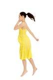 跳跃在黄色礼服的美丽的妇女 免版税图库摄影