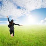 跳跃在绿色米领域和蓝天的愉快的女商人 图库摄影