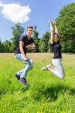 跳跃在绿色草甸的年轻荷兰夫妇 免版税库存图片