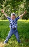 跳跃在绿草的小男孩在公园 免版税库存图片