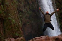 跳跃在Ouzoud瀑布附近的愉快的冒险家在摩洛哥 免版税库存图片