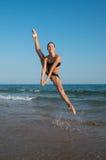 跳跃在t的一个海滩的一位美丽的女性舞蹈家的照片 免版税图库摄影