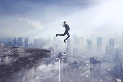 跳跃峭壁的年轻女实业家 库存照片