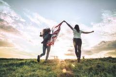 跳跃年轻愉快的女孩跑和无忧无虑与在麦田的开放胳膊 拿着美国旗子 免版税库存图片