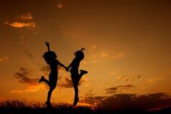 跳跃愉快两名的妇女和日落剪影 库存图片