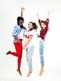 跳跃愉快微笑在白色背景,生活方式人的三个相当年轻不同的国家十几岁的女孩朋友 免版税库存照片