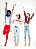跳跃愉快微笑在白色背景,生活方式人的三个相当年轻不同的国家十几岁的女孩朋友 免版税库存图片