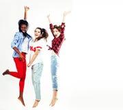 跳跃愉快微笑在白色背景,生活方式人的三个相当年轻不同的国家十几岁的女孩朋友 图库摄影