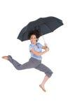 跳跃愉快的优等的女实业家,当拿着伞时 库存图片