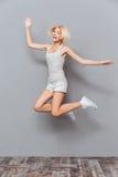 跳跃愉快的可爱的少妇笑和 免版税库存照片