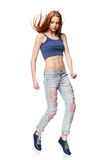 跳跃摆在的困厄的牛仔裤的现代红发女孩 免版税库存照片