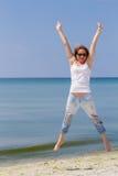 跳跃海滩的愉快的妇女,适合蓝色牛仔裤的运动的健康性感的身体,妇女享用风,自由,假期 库存照片