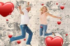跳跃激动的夫妇的综合图象欢呼和 库存图片
