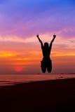 跳跃用手和显示我爱你在海海滩的妇女剪影标志 库存照片
