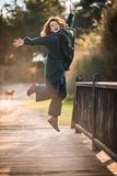 跳跃由在F的一座木老桥梁的Atractive愉快的妇女 库存照片