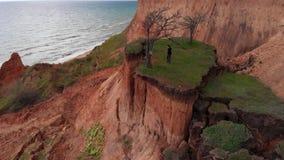 跳跃由山崩倾斜土壤缺点小岛的活跃女孩空中射击靠近海海岸线在多云天气 股票录像