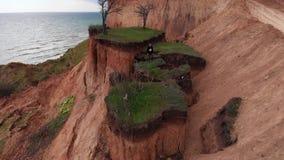 跳跃由山崩倾斜土壤缺点小岛的活跃女孩空中射击靠近海海岸线在多云天气 影视素材