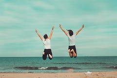 跳跃由海的两个人 乐趣的概念在海滩的 免版税库存图片