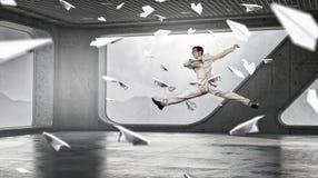 跳跃的商人在办公室 混合画法 免版税库存照片