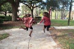 跳跃的女大学生 库存照片