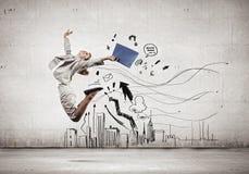 跳跃的女实业家 库存图片