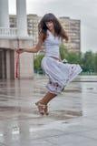 跳跃的微笑的女孩在雨城市背景中 免版税图库摄影