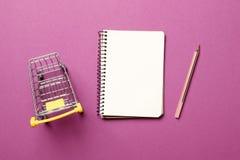 跳跃的推车,有笔的白纸笔记本在桃红色背景 免版税库存照片
