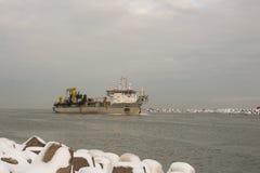 跳跃者进入文茨皮尔斯,拉脱维亚的港撒粉瓶船 免版税库存图片