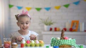 跳跃象兔子从桌下面和看明亮的复活节彩蛋的逗人喜爱的女孩 影视素材