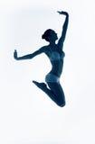 跳跃运动的妇女的蓝色剪影 免版税图库摄影