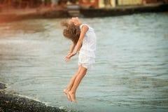 跳跃通过波浪的美丽的女孩 免版税库存图片
