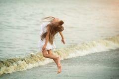 跳跃通过波浪的美丽的女孩 免版税图库摄影