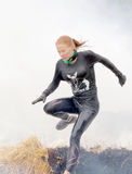 跳跃通过火和烟的白肤金发的妇女 免版税库存照片