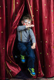跳跃通过阶段帷幕的男孩小丑 免版税库存图片