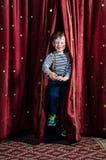 跳跃通过阶段帷幕的男孩小丑 库存图片