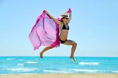 跳跃高与在海滩的一条紫色围巾的年轻幸福妇女 图库摄影