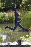 跳跃高为成功的激动的商人在水附近在公园 免版税库存照片